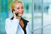 Smiling modern business woman talking on mobile at office building