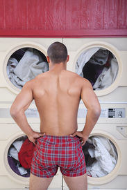 pic of indecent  - Muscular man in boxer shorts waits in front of washing machines - JPG
