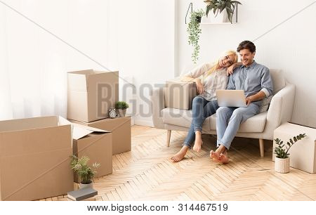 poster of Designing New House. Cheerful Couple Relaxing On Couch With Laptop Among Moving Boxes. Panorama With