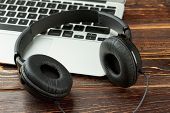 Black Leather Headphones And Laptop. Headphones And Silver Laptop Computer On Wooden Background. Mus poster