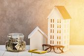 Houses Models On White Wooden Table With Glasses, Calculator And Moneybox In Sunshine, Real Estate C poster