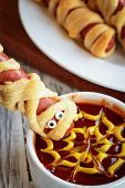 Fun Food For Kids. Mummy Hot Dogs Held Upside Down Over A Bowl Of Ketchup And Mustard Dip, With Spid poster