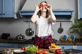 Young Cheerful Girl Prepares A Vegetarian Salad In The Kitchen, The Process Of Preparing Healthy Foo poster