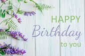 The Inscription Happy Birthday To You With Lilac Wild Flowers In A Curved Wooden Background In Rksti poster