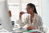 Front view of beautiful mixed-race female graphic designer using graphic tablet at desk in office. M poster