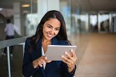 Cheerful Happy Office Worker Using Tablet In Office Hall. Young Latin Business Woman Leaning On Glas poster