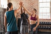 Happy fitness class giving high-five after completing exercise session. Group of multiethnic sporty  poster