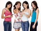 stock photo of foursome  - four pretty young asian women using their phones - JPG