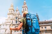 Backpacker Man Pilgrim Looking At Santiago De Compostela Cathedral Standing On The Obradeiro Square  poster