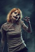 foto of rotten  - Creepy zombie with bloody hands over apocalyptic background - JPG