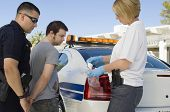 pic of drug dealer  - Police officers arresting drog dealer by police car - JPG