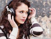 Постер, плакат: Привлекательный счастливый молодая женщина слушать музыку через головы телефоны