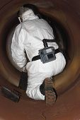 image of ppe  - An engineer wearing  correct ppe for an industrial boiler clean inside the furnance - JPG
