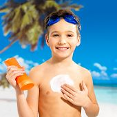 pic of sun-tanned  - Happy schoolchild boy applying sun block cream on the tanned body - JPG
