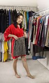 Mature Woman Holding Mini Skirt In Closet