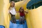 foto of inflatable slide  - Two beautiful little girls having fun on inflatable playground - JPG