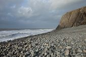 picture of shale  - A pebble beach leads to a shale cliff with waves breaking on the shore and a cloudy sky in the distance - JPG