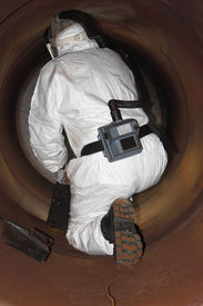stock photo of ppe  - An engineer wearing  correct ppe for an industrial boiler clean inside the furnance - JPG