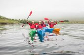 picture of kayak  - Fit friends rowing on a lake in kayaks and cheering at camera - JPG