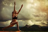 stock photo of surya  - Young woman makes sun salutation yoga exercise - JPG