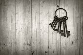 stock photo of locksmith  - bunch of old keys on wooden background black and white - JPG