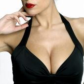 stock photo of cleavage  - Large breasted woman in a black dress - JPG
