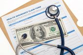 foto of reimbursement  - Medical reimbursement with health insurance claim form and stethoscope on cash isolated - JPG
