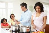 stock photo of saucepan  - Indian Family Cooking Meal At Home - JPG