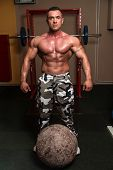 picture of strongman  - Muscular Man Trying To Pick Up A Stone Exercise - JPG