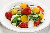 foto of quail egg  - Spinach strawberry orange and quail eggs salad with balsamic vinegar on white plate - JPG