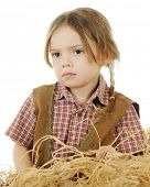 Closeup portrait of a sad preschool cowgirl sitting behind a pile of hay.  On a white background.