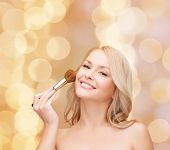 cosmetics, health and beauty concept - beautiful woman with closed eyes and makeup brush