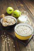 stock photo of porridge  - Porridge oats milk and green apples on the table - JPG