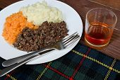 stock photo of haggis  - Traditional Scottish haggis neeps and tatties with whisky also known as a burns supper - JPG