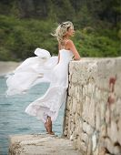 stock photo of windy weather  - Blonde woman stands next to the sea, her dress weaves in the windy weather
