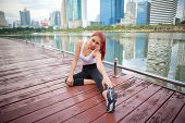 stock photo of hamstring  - Exercise asian woman stretching hamstring leg muscles in city park - JPG