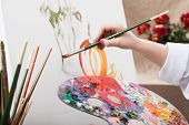 stock photo of masterpiece  - A closeup of an artist with a brush painting a picture - JPG