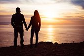 pic of lovers  - Young couple of lovers holding hands towards the sea at sunset - JPG
