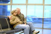 stock photo of sitting a bench  - Senior couple at airport sitting on bench - JPG
