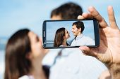picture of selfie  - Young couple on honeymoon travel taking selfie portrait photo with smartphone camera - JPG