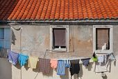 stock photo of laundry  - Clean laundry drying on the rope in front of the old house - JPG