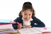 stock photo of hispanic  - Happy little hispanic female girl writing doing homework studying and writing with marker oh notepad with textbooks on desk smiling in children education and back to school concept isolated on white background - JPG