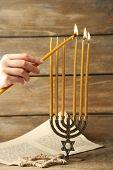 stock photo of menorah  - Hand burning candles on Menorah on wooden background - JPG
