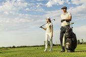 pic of caddy  - Young couple playing golf at golf court at sunny day - JPG