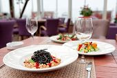 image of squid  - Black squid ink pasta with seafood and other dishes on restaurant table - JPG