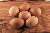 picture of laying eggs  - 6 eggs laying on a wooden chopping board - JPG