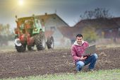 image of farmer  - Young farmer with laptop on the field with seedlings in late autumn - JPG