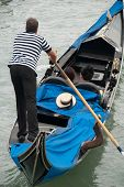 stock photo of gondolier  - venetian gondolier with straw hat and tourists - JPG