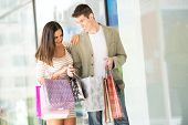 picture of shopping center  - Young happy couple in shopping passes in front of window shopping mall carrying bags in their hands looking in shopping bags - JPG
