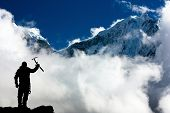 picture of stature  - Silhouette of man with ice axe in hand and mountains with clouds  - JPG